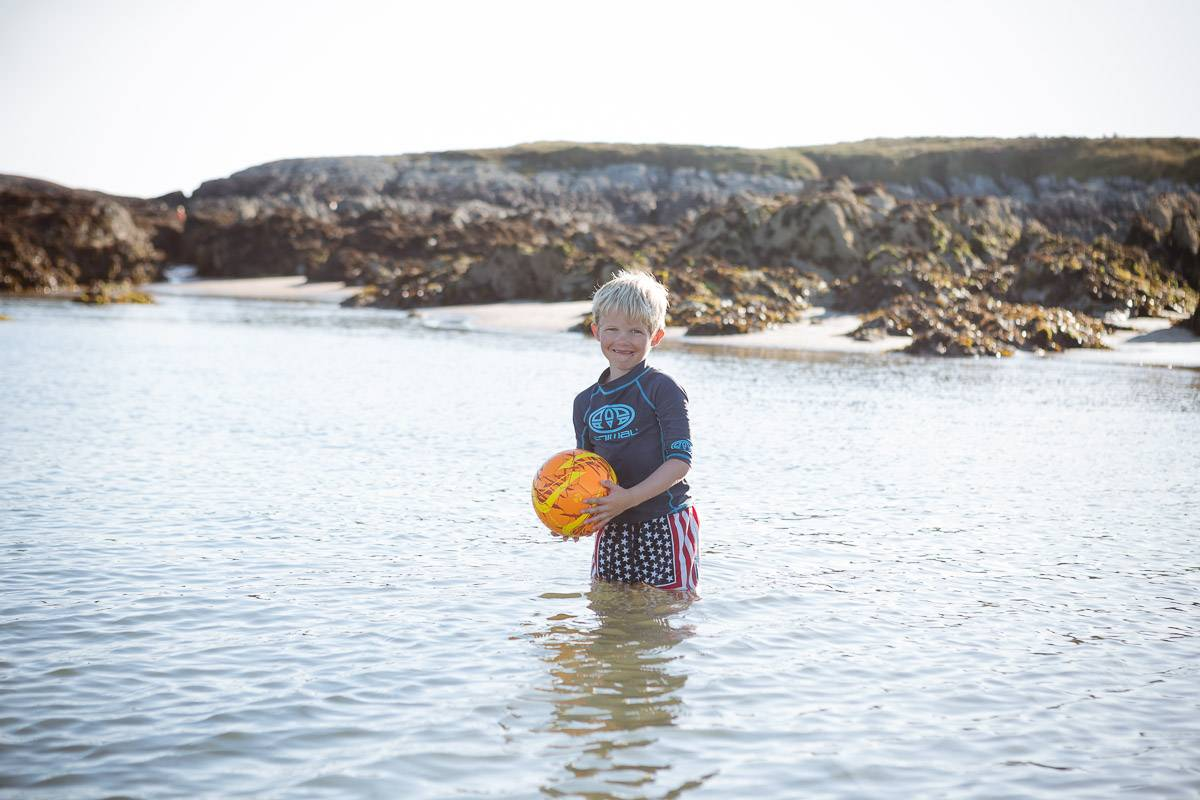 silver-bay-holiday-village-anglesey-young-boy-in-ocean-with-ball.jpg