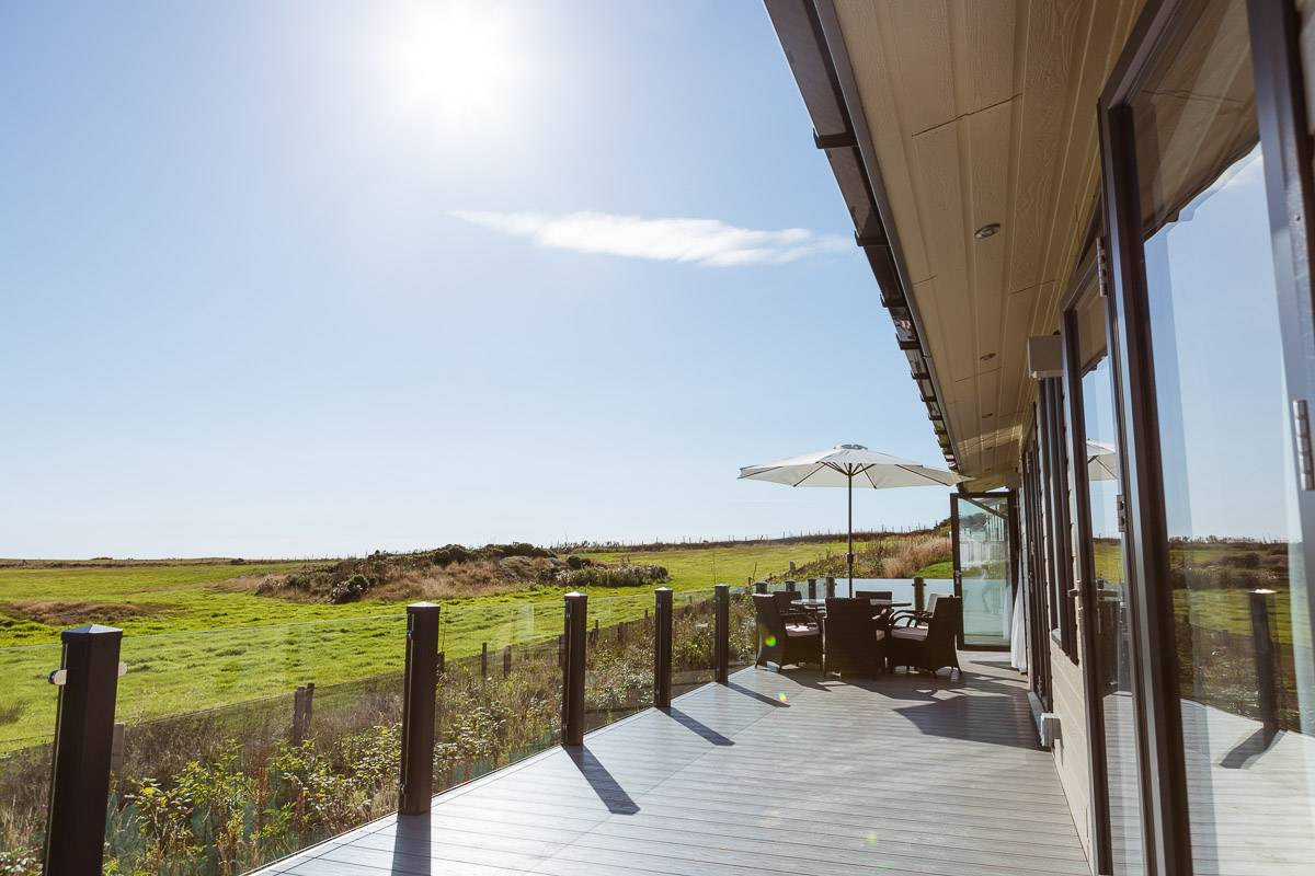 silver-bay-holiday-village-luxury-lodges-anglesey-headland-rise-shearwater-decking-table-sunshine.jpg