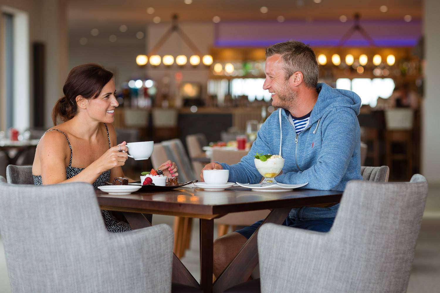 silver-bay-holiday-village-anglesey-the-deck house-couple-having-desserts-coffee