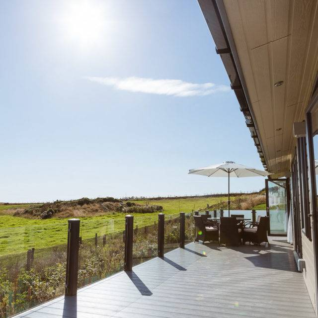 http://silverbay.co.uk/wp-content/uploads/2016/12/silver-bay-holiday-village-luxury-lodges-anglesey-headland-rise-shearwater-decking-table-sunshine-640x640.jpg