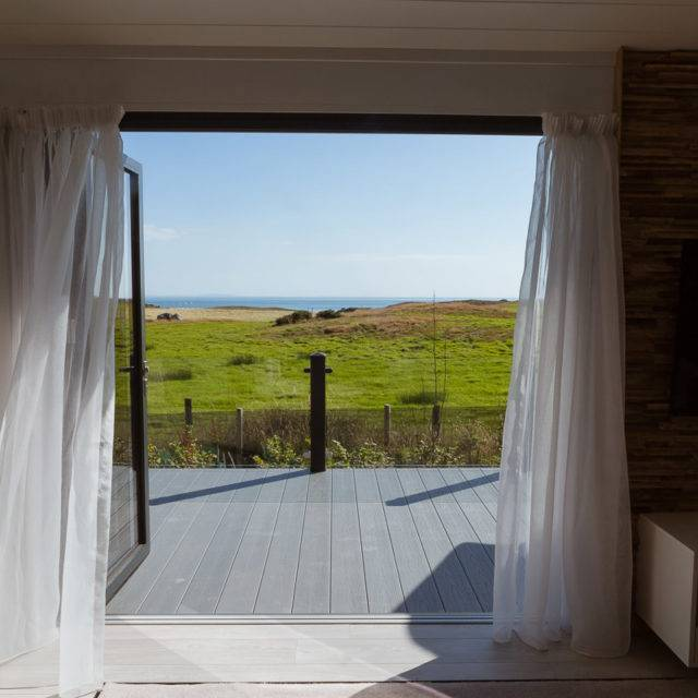 https://silverbay.co.uk/wp-content/uploads/2016/12/silver-bay-holiday-village-luxury-lodges-anglesey-headland-rise-shearwater-the-view-grass-blue-skies-640x640.jpg