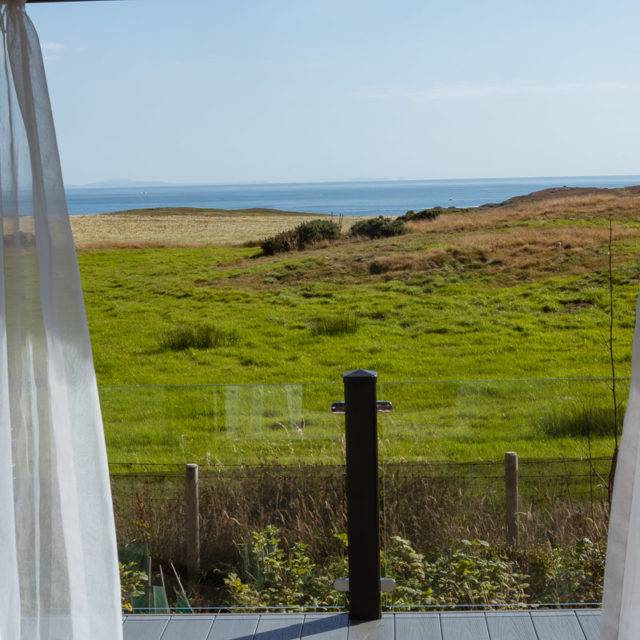 https://silverbay.co.uk/wp-content/uploads/2016/12/silver-bay-holiday-village-luxury-lodges-anglesey-headland-rise-shearwater-the-view-ocean-grass-sand-640x640.jpg