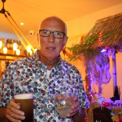 man enjoying summer party with two drinks