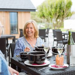 silver-bay-holiday-village-anglesey-the-deck house-women-dining-outdoors